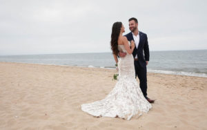 Happy bride and groom smiling while on a Cape Cod beach