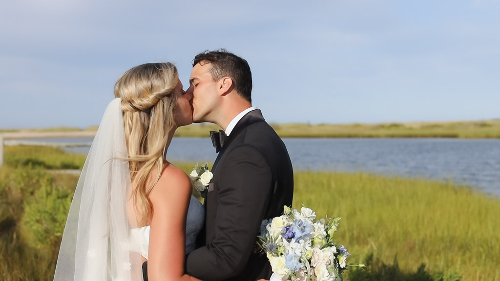 Martha's Vineyard wedding couple sharing a kiss by the water