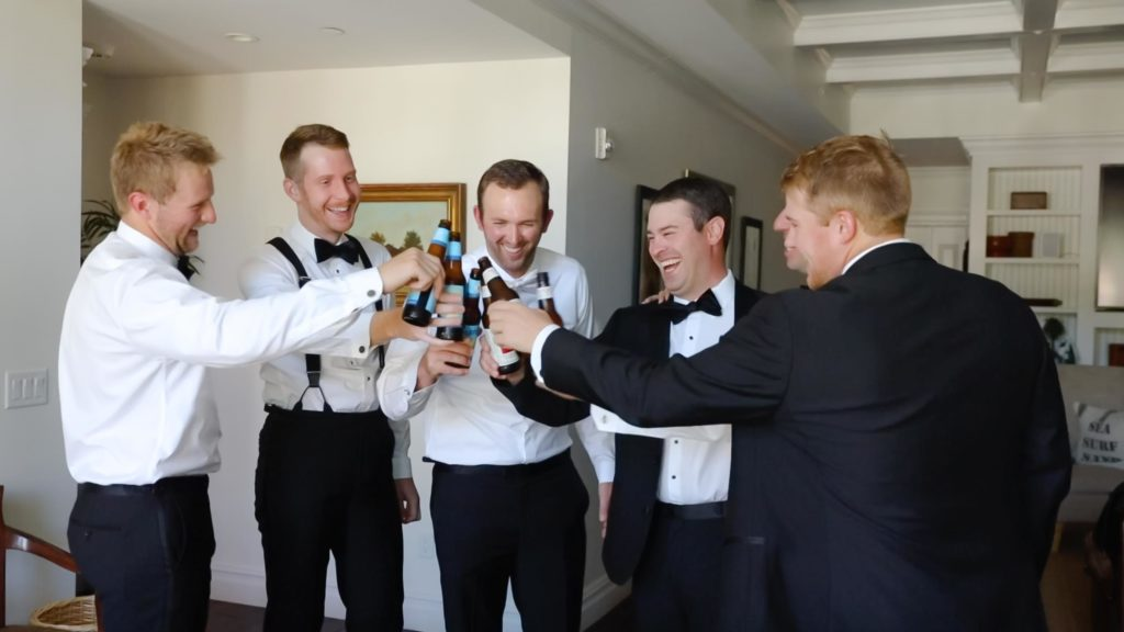 Groomsmen toasting to the groom in their rented luxury Airbnb in Chatham MA