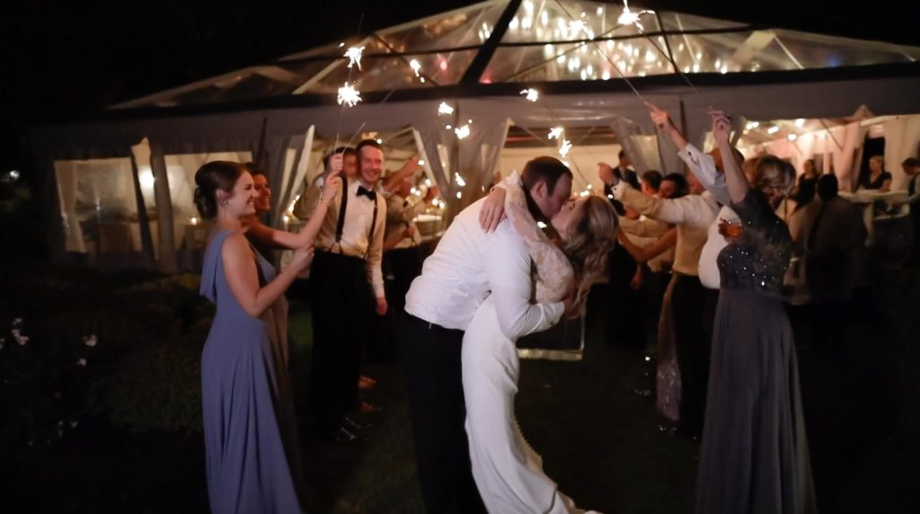 Bride and groom have sparkler exit outside glass ceiling tent at Wequassett Resort and Golf Club on Cape Cod
