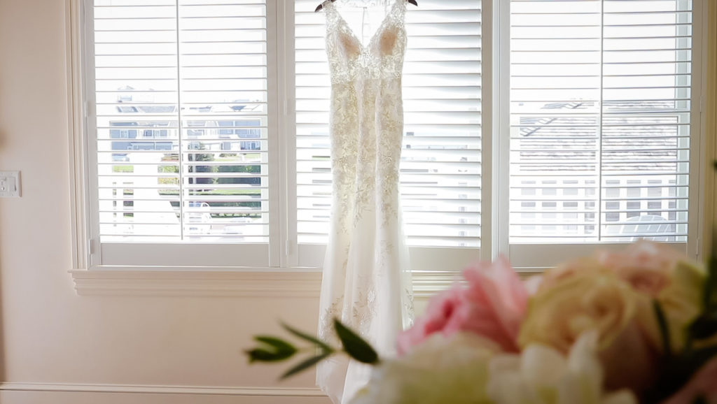 Wedding dress hanging on quintessential Cape Cod window frame.