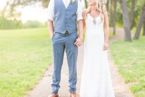bride and groom holding hands on path