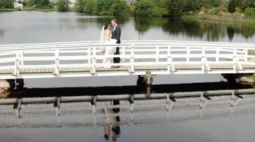 Cassidy + John Popponesset Inn Wedding with their first look on a nearby bridge